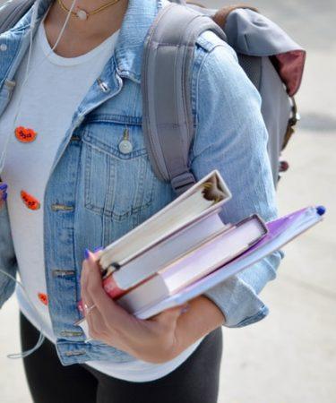 étudiante qui porte des livre avec son sac à dos